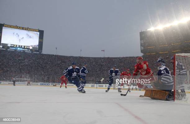 Dion Phaneuf of the Toronto Maple Leafs and Daniel Alfredsson of the Detroit Red Wings pursue the puck in overtime during the 2014 Bridgestone NHL...