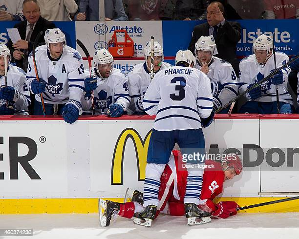 Dion Phaneuf of the Toronto Maple Leafs body checks Stephen Weiss of the Detroit Red Wings during a NHL game on December 10 2014 at Joe Louis Arena...