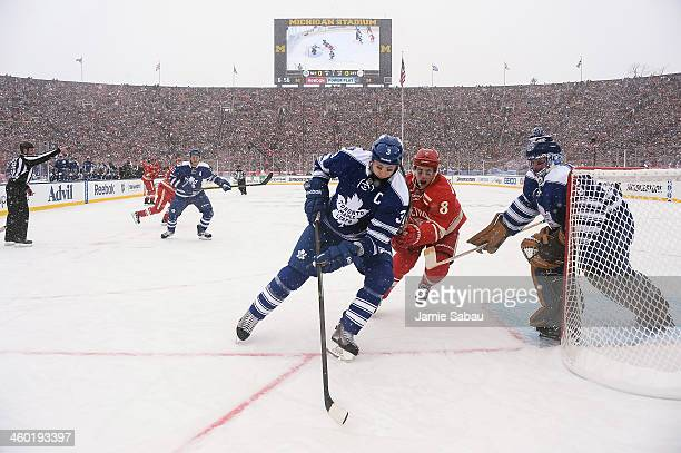Dion Phaneuf of the Toronto Maple Leafs controls the puck as Justin Abdelkader of the Detroit Red Wings defends near goaltender Jonathan Bernier of...