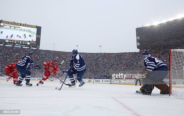 Dion Phaneuf of the Toronto Maple Leafs controls the puck in the low slot area as Daniel Cleary of the Detroit Red Wings pursues the play in the...