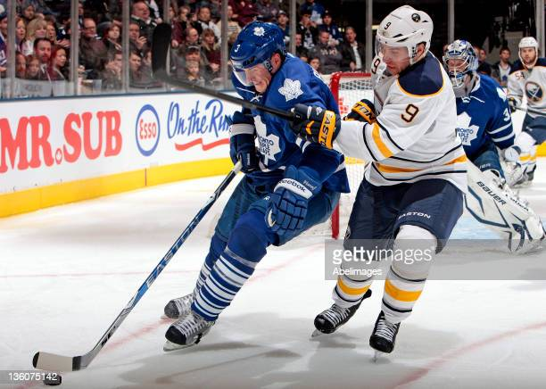 Dion Phaneuf of the Toronto Maple Leafs gets around Derek Roy of the Buffalo Sabres during NHL action at The Air Canada Centre December 22 2011 in...