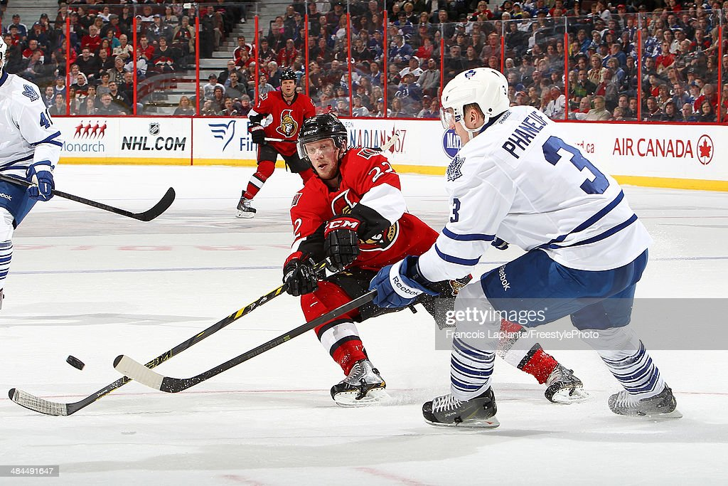 Dion Phaneuf #3 of the Toronto Maple Leafs passes the puck against Erik Condra #22 of the Ottawa Senators on April 12, 2014 at Canadian Tire Centre in Ottawa, Ontario, Canada.