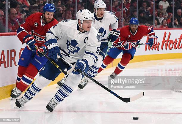 Dion Phaneuf of the Toronto Maple Leafs skates with the puck against Brandon Prust the Montreal Canadiens in the NHL game at the Bell Centre on...