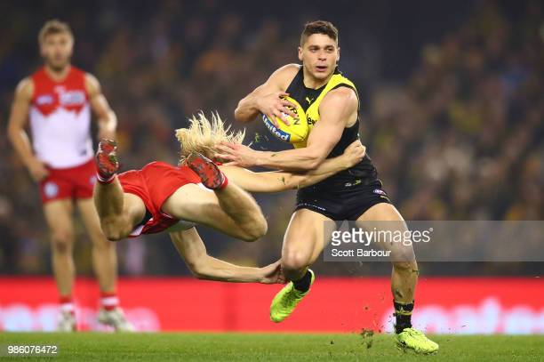 Dion Prestia of the Tigers is tackled by Harry Cunningham of the Swans during the round 15 AFL match between the Richmond Tigers and the Sydney Swans...