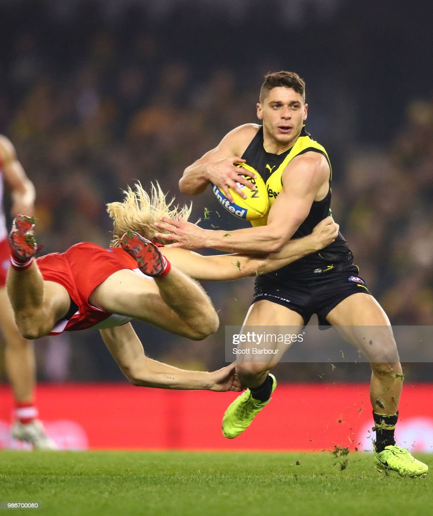 Dion Prestia of the Tigers is tackled by Harry Cunningham of the Swans during the round 15 AFL match between the Richmond Tigers and the Sydney Swans at Etihad Stadium on June 28, 2018 in Melbourne, Australia.