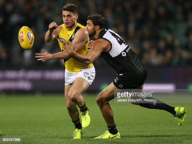 Dion Prestia of the Tigers is tackled by Paddy Ryder of the Power during the 2017 AFL round 15 match between the Port Adelaide Power and the Richmond...