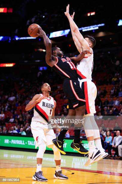 Dion Waiters of the Miami Heat goes up against CJ McCollum and Zach Collins of the Portland Trail Blazers in the first quarter at American Airlines...