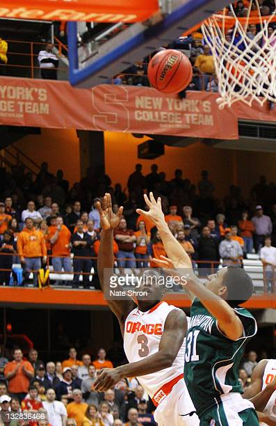 Dion Waiters of the Syracuse Orange shoots the ball against Michael Alvarado of the Manhattan College Jaspers during the NIT Season Tipoff game at...