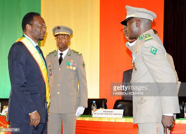 Dioncounda Traore the former parliament speaker receives a salute from junta leader captain Amadou Sanogo during his swearing in ceremony as Mali's...