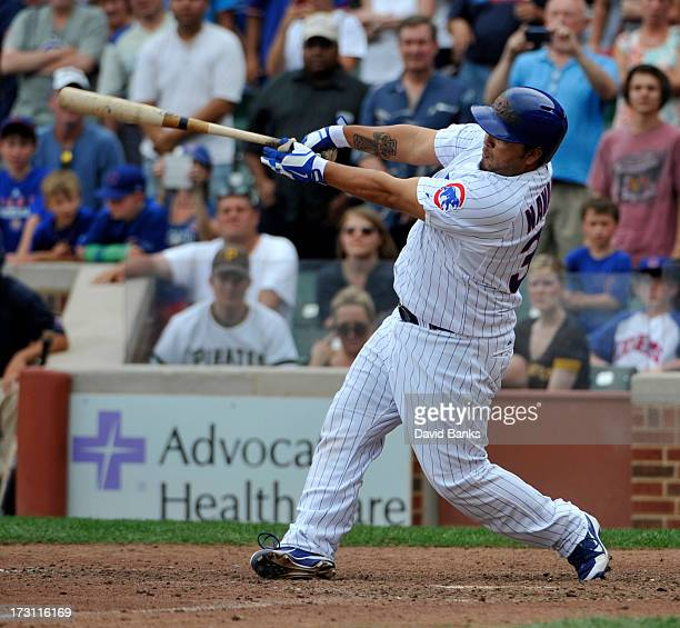 Dioner Navarro of the Chicago Cubs hits a walkoff sacrifice fly against the Pittsburgh Pirates during the eleventh inning on July 7 2013 at Wrigley...