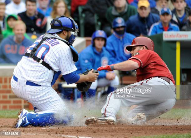 Dioner Navarro of the Chicago Cubs tags out Jason Kubel of the Arizona Diamondbacks during the third inning on June 2 2013 at Wrigley Field in...
