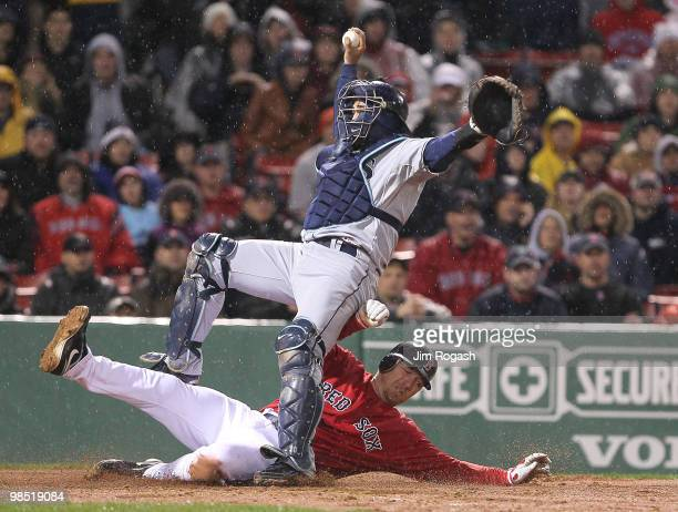 Dioner Navarro of the Tampa Bay Rays falls as JD Drew of the Boston Red Sox is out on a fielder's choice in the 11th inning at Fenway Park on April...