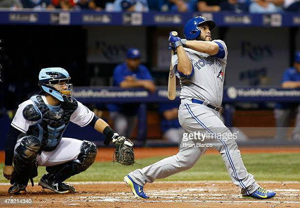 Dioner Navarro of the Toronto Blue Jays hits a home run in front of catcher Rene Rivera of the Tampa Bay Rays during the fifth inning of a game on...