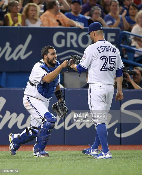 Dioner Navarro of the Toronto Blue Jays is congratulated by Marco Estrada after catching a foul pop up in the third inning during MLB game action...