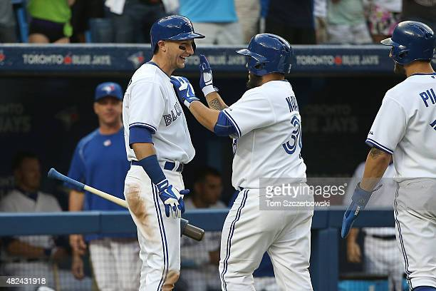 Dioner Navarro of the Toronto Blue Jays is congratulated by Troy Tulowitzki after hitting a tworun home run in the second inning during MLB game...