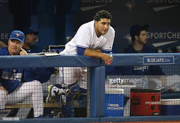 Dioner Navarro of the Toronto Blue Jays looks on from the top step of the dugout during MLB game action against the Chicago Cubs on September 9 2014...