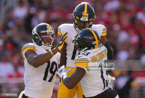 Diontae Johnson, James Washington and JuJu Smith-Schuster of the Pittsburgh Steelers celebrate after Johnson caught a 39-yard touchdown pass against...