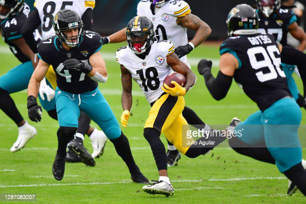 Diontae Johnson of the Pittsburgh Steelers carries the ball as Joe Schobert of the Jacksonville Jaguars defends during the first half at TIAA Bank...
