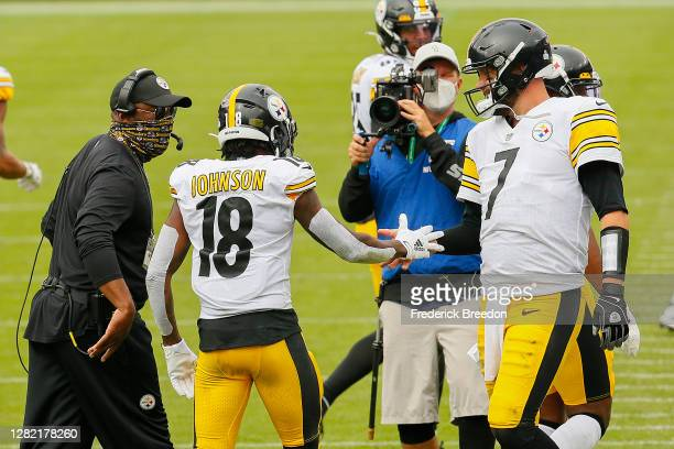 Diontae Johnson of the Pittsburgh Steelers is congratulated by teammate Ben Roethlisberger and head coach Mike Tomlin after scoring a touchdown...