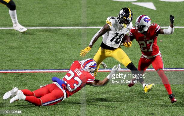 Diontae Johnson of the Pittsburgh Steelers is tackled by Micah Hyde and Tre'Davious White of the Buffalo Bills during the fourth quarter in the game...