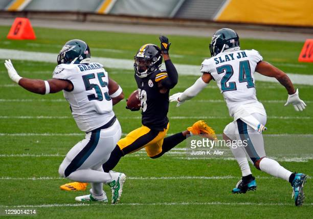 Diontae Johnson of the Pittsburgh Steelers runs after the catch against Brandon Graham and Darius Slay of the Philadelphia Eagles during the first...