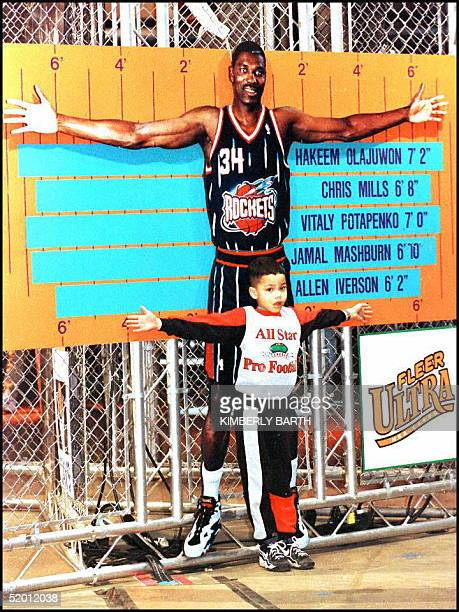 Dionte Neves of Mentor OH measures his arm span against the likeness of NBA player Hakeem Olajuwon of the Houston Rockets 06 February at the AllStar...