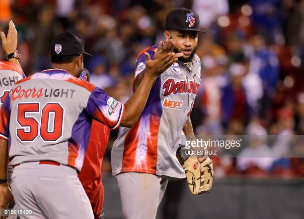 Dionys Cesar and Ronny Rodriguez of Aguilas Cibaenas of Republica Dominicana celebrate their victory against Alazanes del Granma of Cuba during the...