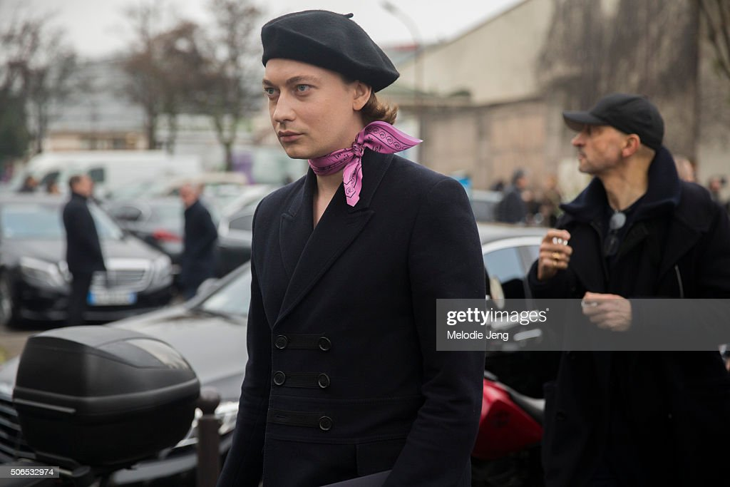 A Dior Homme showgoer wears a black beret and pink handkerchief/bandana around their neck on January 23, 2016 in Paris, France.