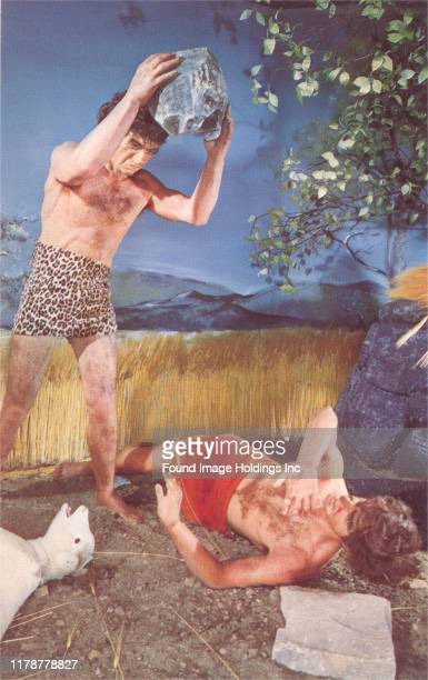 A diorama depicting two cavemen fighting with a rock