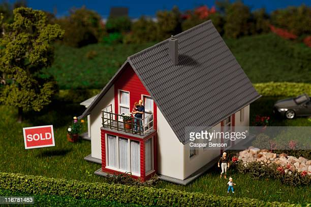 A diorama of a miniature house with a family of figurines and a SOLD sign
