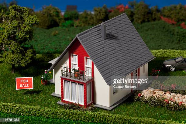 A diorama of a miniature house with a FOR SALE sign