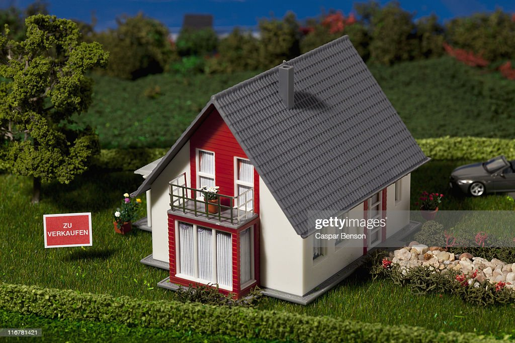 A diorama of a miniature house with a  ZU VERKAUFEN (for sale in German) sign : Stock Photo