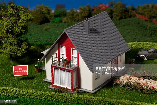 A diorama of a miniature house with a  ZU VERKAUFEN (for sale in German) sign