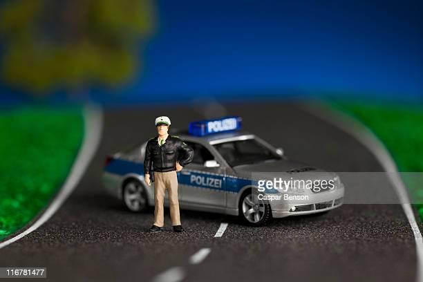 A diorama of a miniature policeman figurine standing by a miniature police car