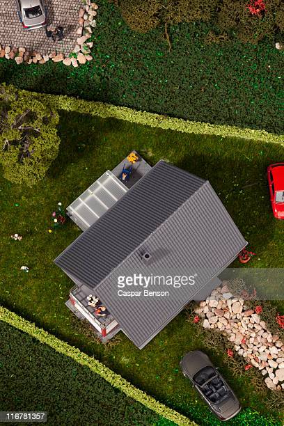 A diorama of miniature cars, people and a house, directly above