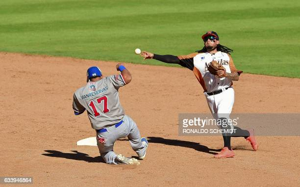 Diory Hernandez of Tigres del Licey of the Dominican Republic tags out in second base Freddy Galvis of Aguilas del Zulia of Venezuela during the...