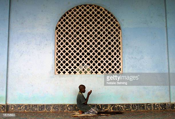 Dioula youth prays in the Grand Mosque March 3 2003 in Agboville north of Abidjan Ivory Coast The civil war has divided the country between the more...