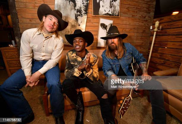 Diplo Lil Nas X Billy Ray Cyrus pose backstage during the 2019 Stagecoach Festival at Empire Polo Field on April 28 2019 in Indio California