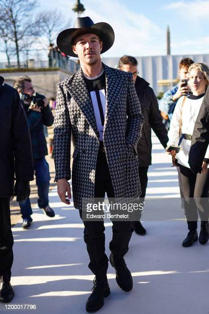Diplo wears a cowboy hat, a jacket with printed geometric patterns, a t-shirt, outside Vuitton, during Paris Fashion Week - Menswear Fall / Winter...