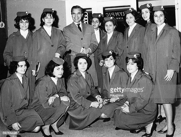 Diplomat and racing driver Porfirio Rubirosa surrounded by a group of air hostesses for Olympic Airways at Ellinikon Airport Athens circa 1965