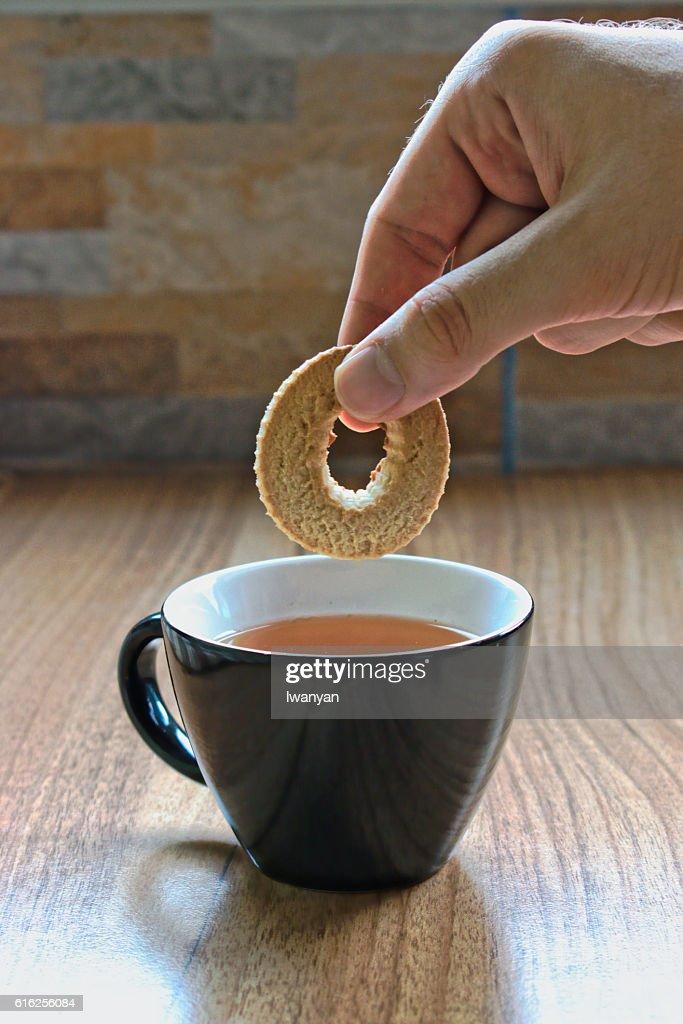 Dipping a Cookie into Tea : Foto de stock