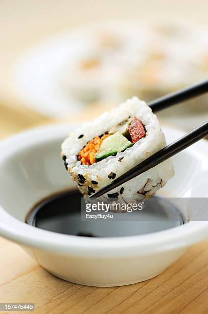 dipping california roll sushi - soy sauce stock pictures, royalty-free photos & images