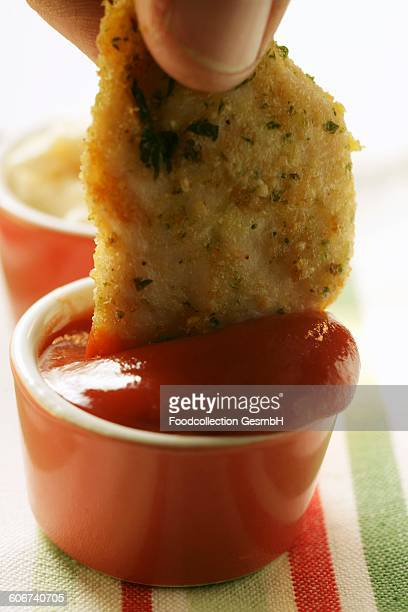 Dipping chicken nugget into ketchup