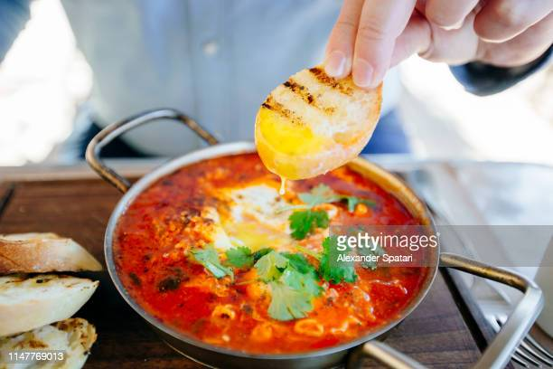 dipping fresh bread in shakshuka, close up - tel aviv foto e immagini stock