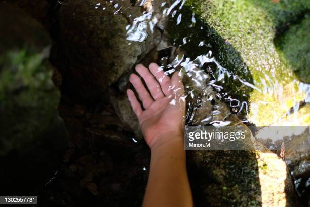 dipping hand in the clean spring water - 湧水 ストックフォトと画像