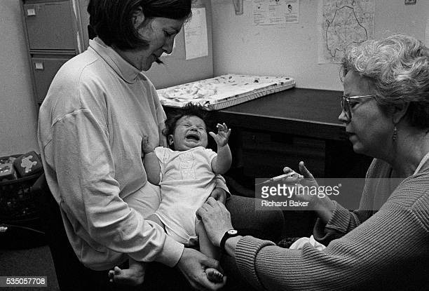 Diptheria tetanus polio whooping cough meningitis A four monthold baby screams with the sharp prick of an innoculation needle administered by a...