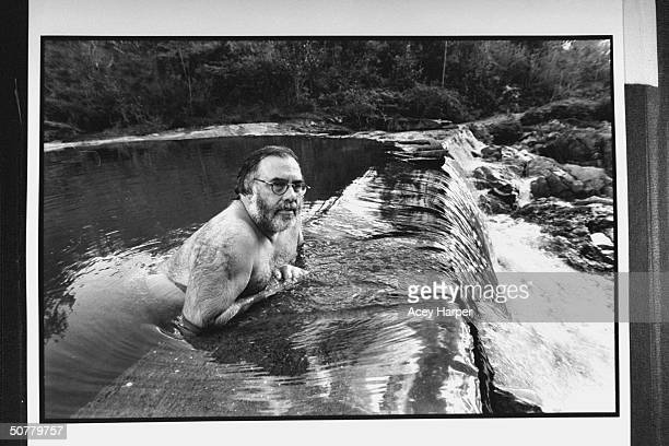 Dir Francis Ford Coppola wading in a natural pool while leaning on a rock of a waterfall near his Blancaneaux Lodge