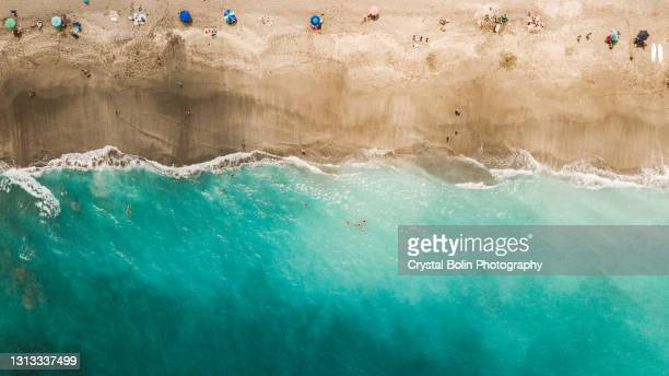 direct aerial overview of a vibrant teal ocean seashore and colorful beach umbrellas on jupiter, florida at mid-day during covid-19 in april of 2021 - jupiter florida stock pictures, royalty-free photos & images