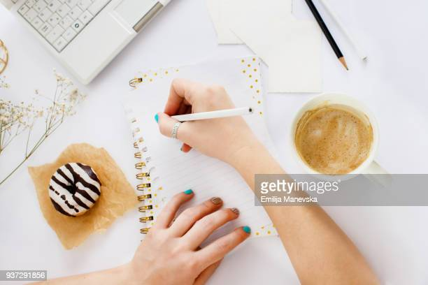direct view at woman's hands writing on a blank paper - list stock pictures, royalty-free photos & images