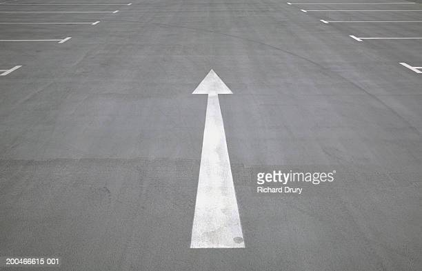direction arrow on ground in car park - richard drury stock pictures, royalty-free photos & images